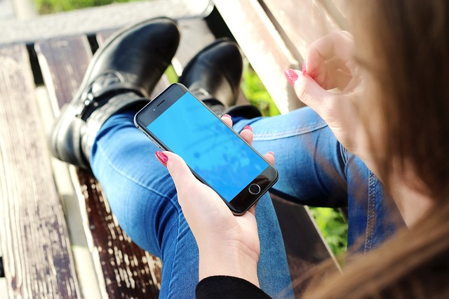 A woman sitting outside on her smart phone