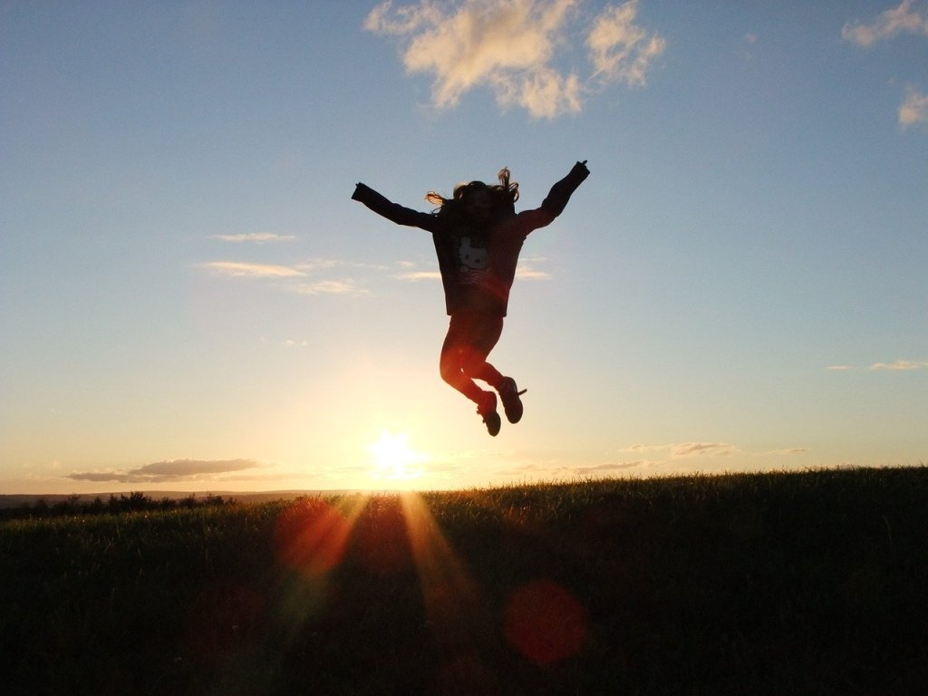 person jumping at sunset